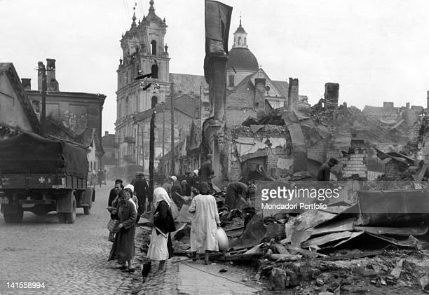 Latvian people rummaging through the rubble of buildings burned by retreating Russian troops. Riga, June 1941