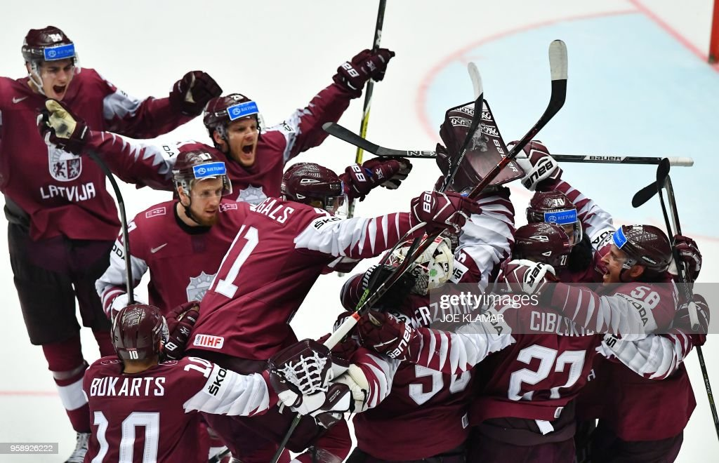TOPSHOT - Latvian players celebrate their 1-0 victory after the group B match Latvia v Denmark of the 2018 IIHF Ice Hockey World Championship at the Jyske Bank Boxen in Herning, Denmark, on May 15, 2018.