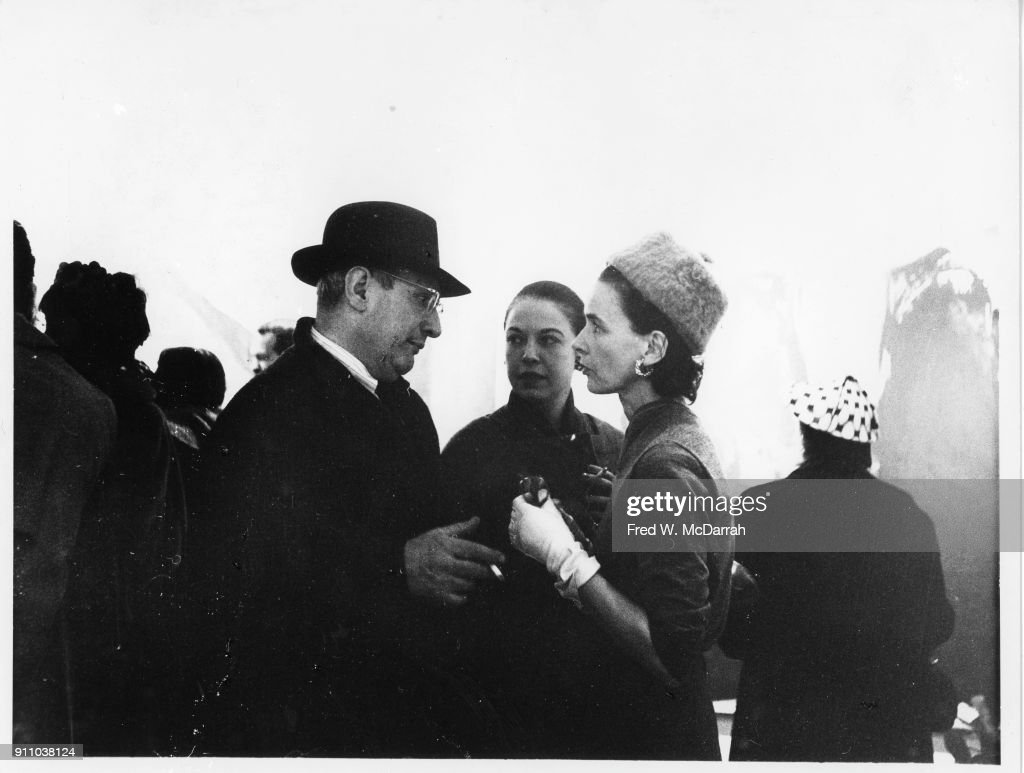 Latvian-born American painter Mark Rothko (1903 - 1970), Betsy Zogbaum (born Elizabeth Ross), and an unidentified woman talk together at Sidney Janis Gallery, New York, New York, March 9, 1959.