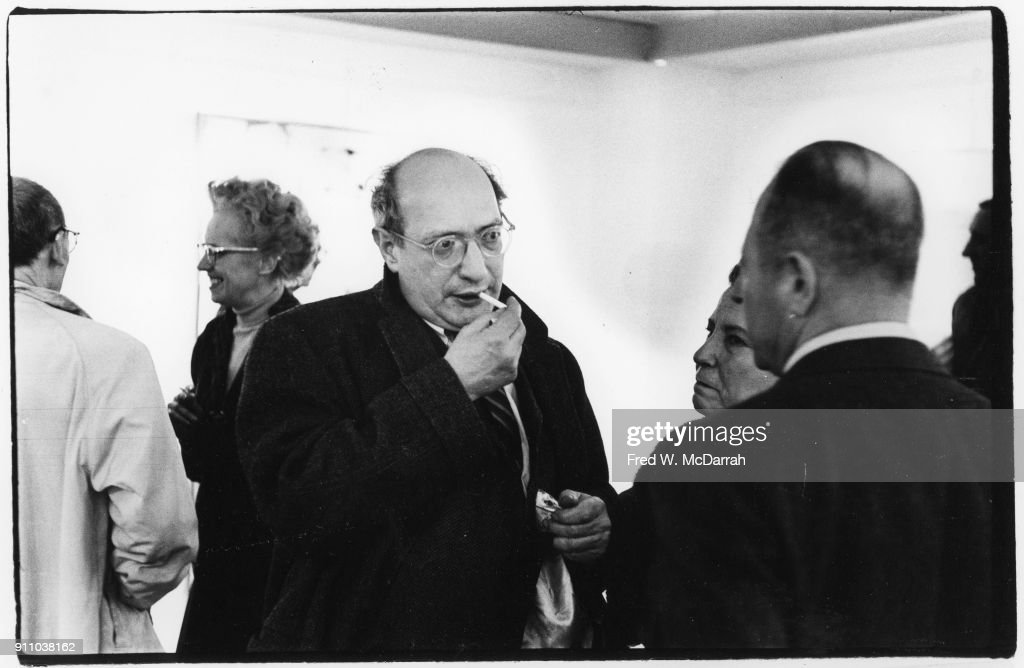 Latvian-born American painter Mark Rothko (1903 - 1970) (center) lights a cigarette as he talks to unidentified others during an exhibition at Sidney Janis Gallery, New York, New York, March 6, 1961.