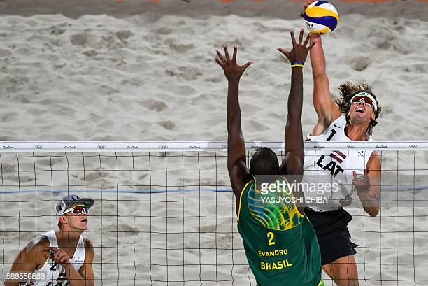 Latvia's Aleksandrs Samoilovs spikes the ball during the men's beach volleyball qualifying match between Brazil and Latvia at the Beach Volley Arena...