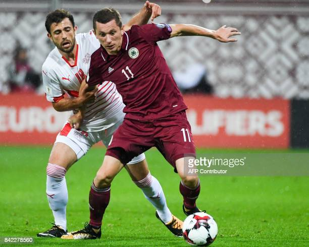 Latvia's Aleksandrs Solovjovs fights for the ball with Switzerland's Admir Mehmedi during the WC2018 group B qualifying football match between Latvia...