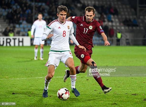 Latvia's Arturs Zjuzins vies with Hungray's Adam Nagy during the WC 2018 football qualification match between Latvia and Hungary in Riga on October...