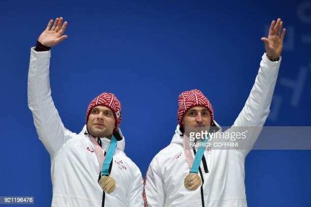Latvia's bronze medallists Oskars Melbardis and Janis Strenga pose on the podium during the medal ceremony for the 2man bobsleigh at the Pyeongchang...