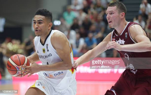 Latvia's Dairis Bertans and Germany's Maodo Lo vie for the ball during the Supercup basketball match between Germany and Latvia in Hamburg Germany 21...