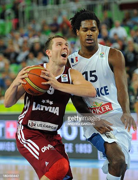 Latvia's Dairis Bertans fights for the ball with France's Mickael Gelabale on September 13 2013 during a 2013 EuroBasket Championship second round...