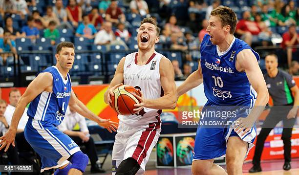 Latvia's Dairis Bertans vies with Czech Republic's Petr Benda and Pavel Houska during the 2016 FIBA World Olympic Qualifying basketball match between...