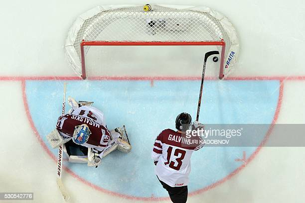 Latvia's defender Guntis Galvins takes the puck out of the net of Latvia's goalie Edgars Masalskis following a goal during the group A preliminary...