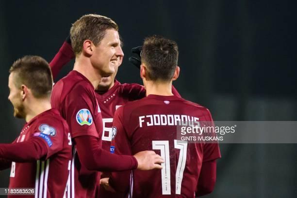 Latvia's defender Kaspars Dubra and team mates celebrate winning the UEFA Euro 2020 Group G qualification football match Latvia v Austria in Riga...