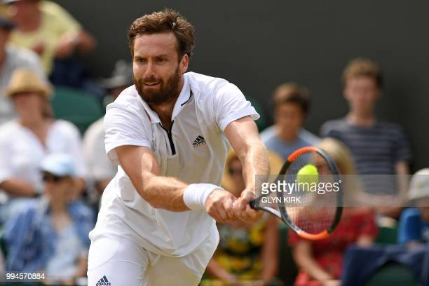 Latvia's Ernests Gulbis returns against Japan's Kei Nishikori during their men's singles fourth round match on the seventh day of the 2018 Wimbledon...
