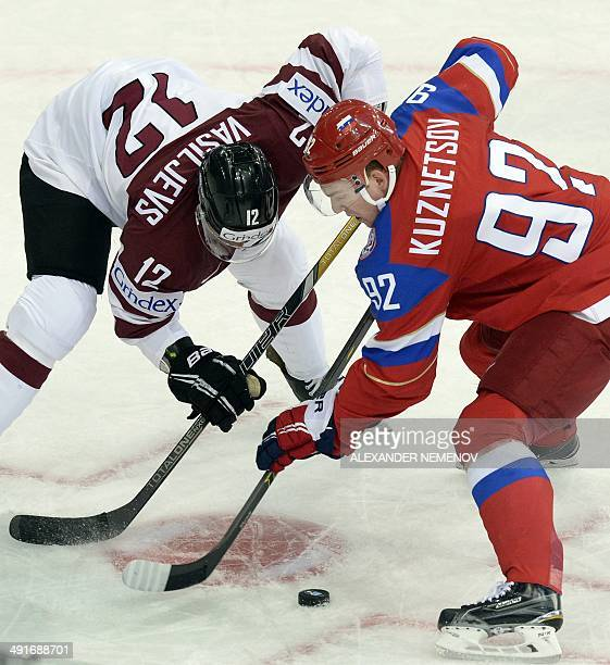 Latvia's forward Herberts Vasiljevs faces off with Russia's forward Yevgeni Kuznetsov during the preliminary round group B game Latvia vs Russia of...