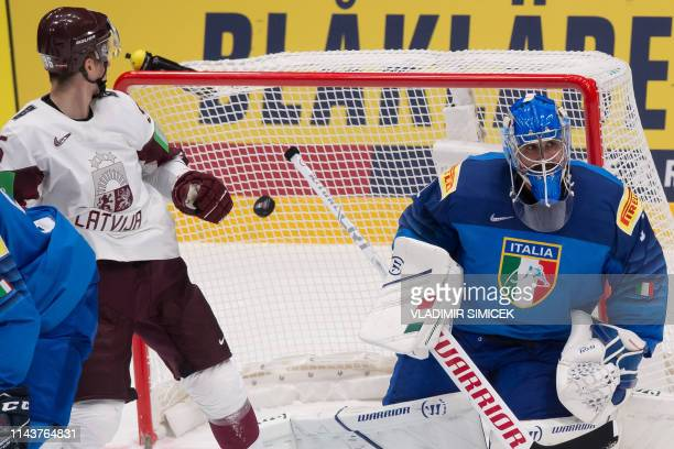 Latvias forward Maris Bicevskis eyes the puck entering the cage next to Italys goalkeeper Andreas Bernard during the IIHF Men's Ice Hockey World...