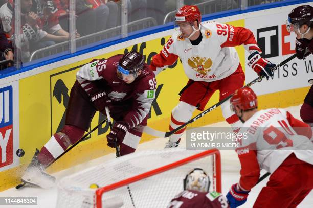 Latvia's forward Oskars Batna and Russia's forward Yevgeny Kuznetsov vie for the puck during the World Championships Group B match between Latvia and...