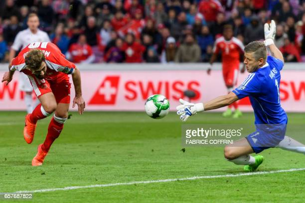 Latvia's goalkeeper Andris Vanins deflect a shot in front of Swiss forward Admir Mehmedi during the WC 2018 qualifying football match Switzerland vs...