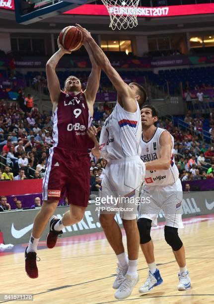 Latvia's guard Dairis Bertans vies for the ball with Serbia's guard Bogdan Bogdanovic and center Boban Marjanovic during FIBA Eurobasket 2017 men's...