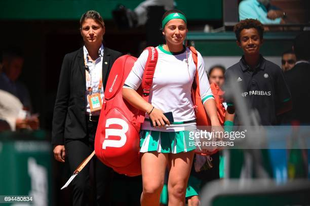 Latvia's Jelena Ostapenko arrives on the court with a ball boy before her final tennis match against Romania's Simona Halep at the Roland Garros 2017...