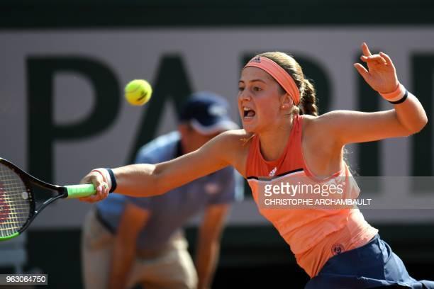 Latvia's Jelena Ostapenko plays a return to Ukraine's Kateryna Kozlova during their women's singles first round match on day one of The Roland Garros...