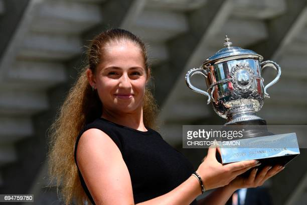 TOPSHOT Latvia's Jelena Ostapenko poses on June 11 2017 with her trophy after winning her final tennis match against Romania's Simona Halep on June...