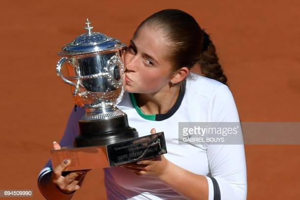 Latvia's Jelena Ostapenko poses with the trophy after winning against Romania's Simona Halep during their final tennis match at the Roland Garros...