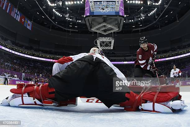 Latvia's Lauris Darzins vies with Canada's goalkeeper Carey Price during the Men's Ice Hockey Quarterfinals Canada vs Latvia at the Bolshoy Ice Dome...
