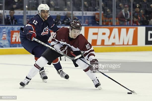 Latvia's Martins Dzierkals stick handles past United States' Jordan Greenway . Team USA vs Team Latvia in 1st round action of 2017 IIHF Junior...