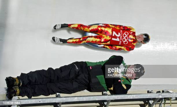 Latvia's Martins Rubenis speeds through the ice channel near a member of the olympic staff during a training in the men's singles luge during the...