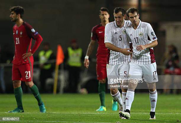 Latvia's midfielder Arturs Zjuzins from Latvia celebrates with teammate Latvia's midfielder Oleg Laizane from Latvia after scoring a goal during the...