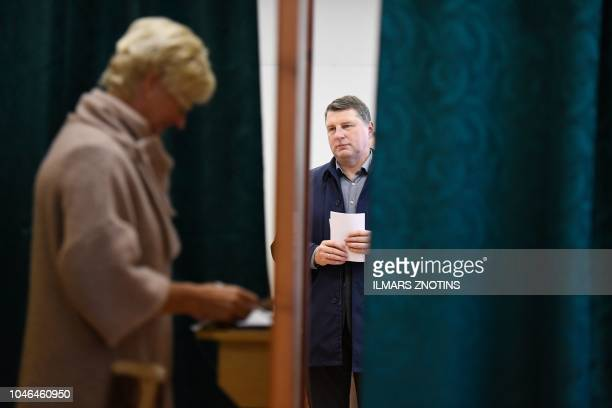 Latvia's President Raimonds Vejonis lines up to cast his ballot at a polling station in Ogre Latvia during general elections on October 6 2018
