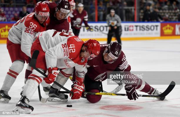 Latvia´s Teodors Blugers and Denmark´s Mikkel Aagaard vie for the puck during IIHF Ice hockey world championship first round match between Latvia and...
