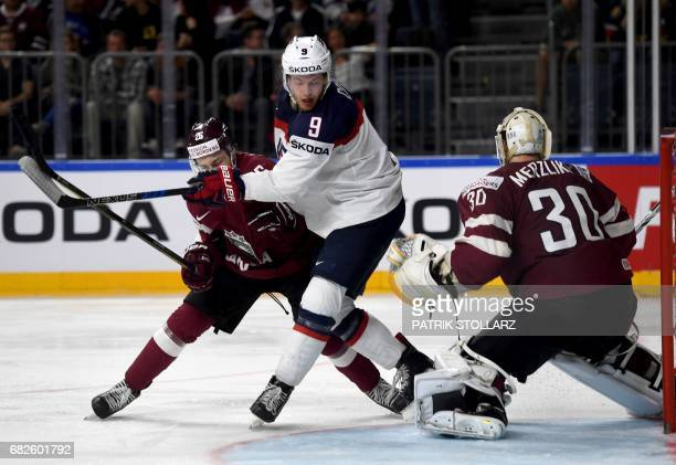 Latvia's Uvis Balinskis and Elvis Merzlikins vie for the puck with the US' Andrew Copp during the IIHF Men's World Championship ice hockey match...