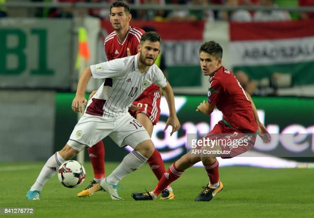 Latvia's Valerijs Sabala vies with Hungary's Barnabas Bese and Adam Nagy during the FIFA World Cup 2018 qualification football match between Hungary...