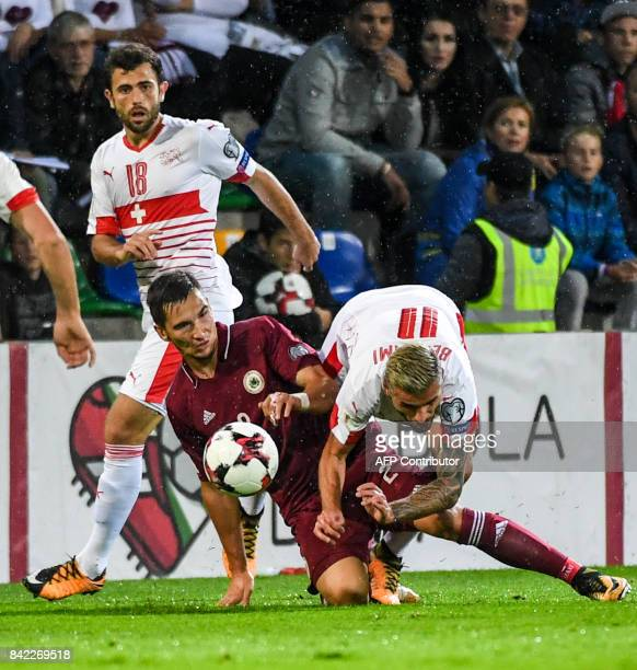 Latvia's Vitalijs Maksimenko and Switzerland's Valon Behrami vie for the ball during the FIFA World Cup 2018 qualification football match between...