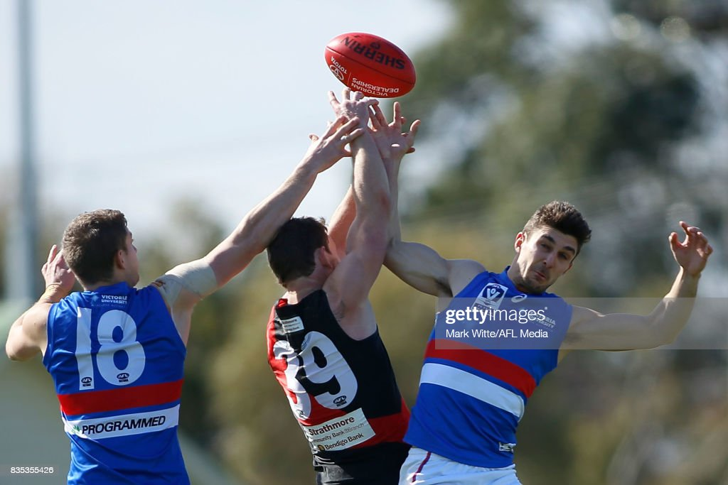 Lauchlan Dalgleish and Fletcher Roberts of Footscray Bulldogs go to spoil Heath Hocking of Essendon Bombers during the round 18 VFL match between the Essendonf Bombers and Footscray Bulldogs at Windy Hill on August 19, 2017 in Melbourne, Australia.
