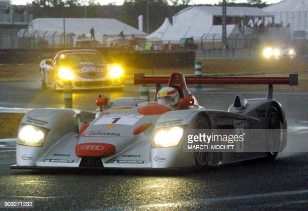 l'Audi R8 n°1 pilotée par l'Allemand Franck Biela le Danois Tom Kristensen et l'Italien Emanuele Pirro négocie un virage sous la pluie le 16 juin...