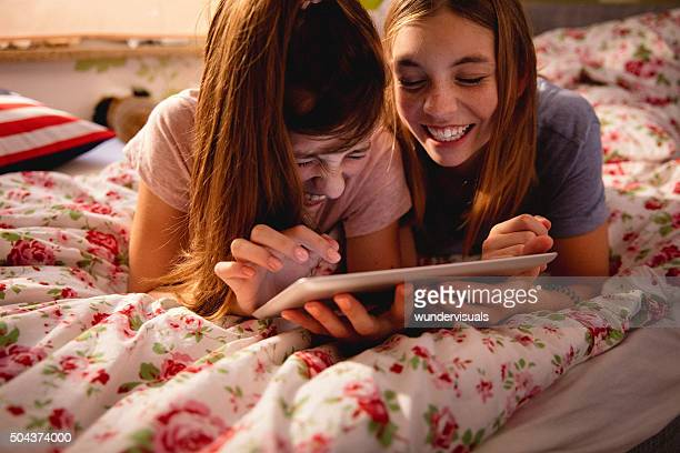 Laughing adolescent girls sharing something funny on a digital tablet