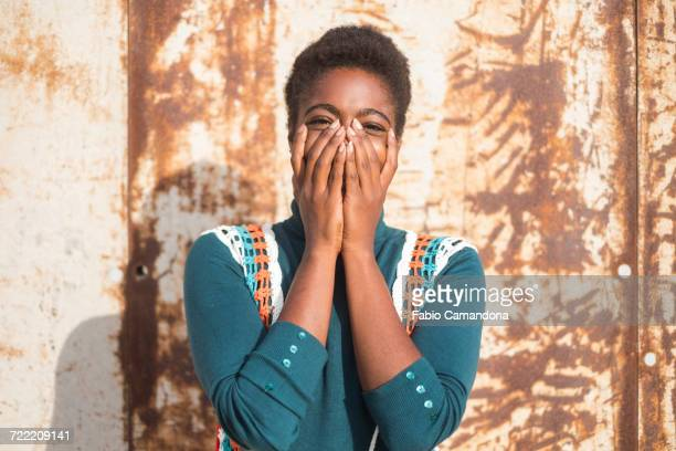 Laughing African American woman with head in hands