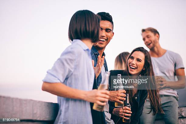 Laughing and drinking with friends on a summer rooftop party