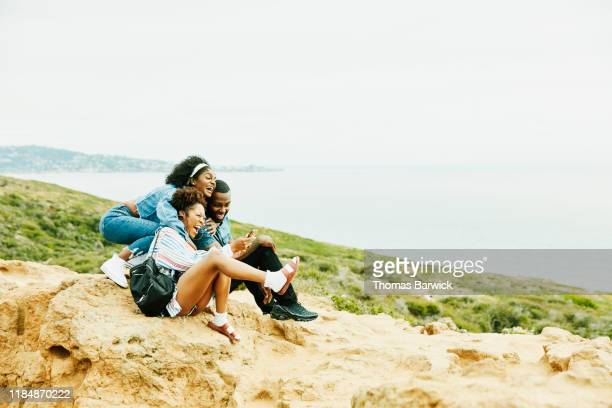 laughing and embracing friends taking selfie with smart phone while sitting at ocean lookout in park - public park photos et images de collection