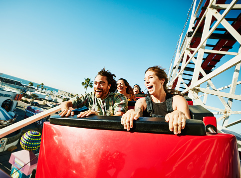 Laughing and screaming couple riding roller coaster at amusement park - gettyimageskorea