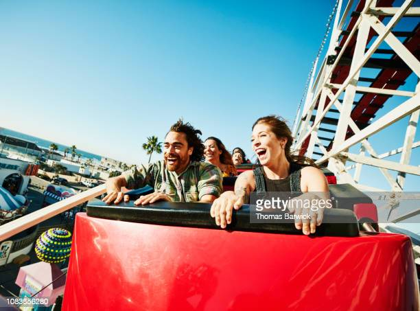 laughing and screaming couple riding roller coaster at amusement park - arts culture and entertainment photos stock photos and pictures