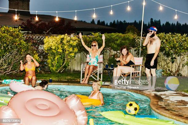 Laughing and smiling friends hanging out together during backyard pool party on summer evening