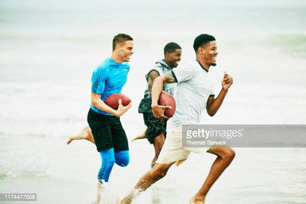 laughing and smiling friends running race through water on beach - rush american football stock pictures, royalty-free photos & images
