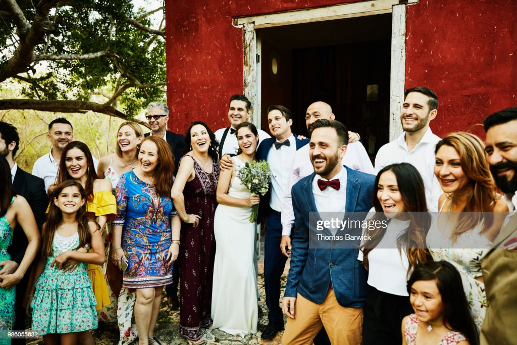 Laughing and smiling wedding party posing for group photo in front of chapel after wedding ceremony : Stock Photo