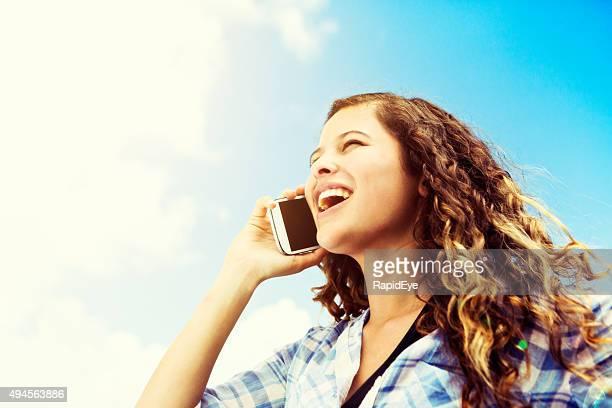 Rire, animée et jeune beauté discuter sur un smartphone à l'extérieur