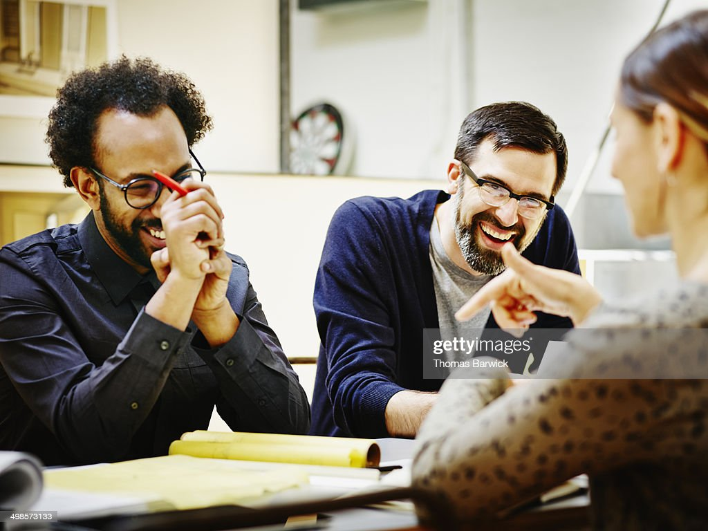 Laughing architects at conference table in office : Stock Photo