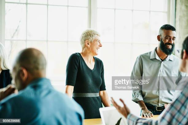 laughing architects in design planning meeting in office conference room - rolled up sleeves stock photos and pictures
