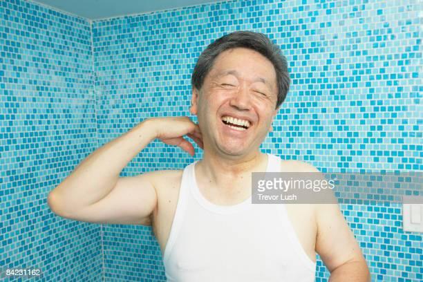 Laughing Asian man in bathroom