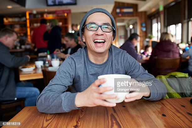 Laughing Asian man in coffee shop