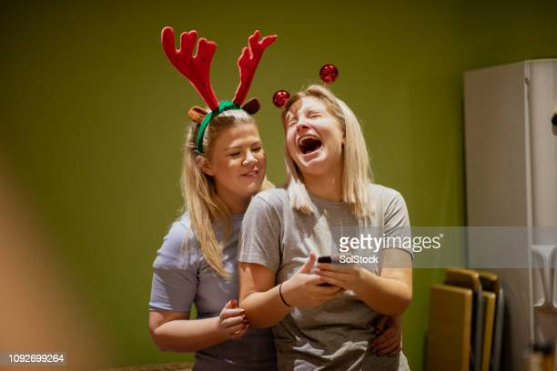 laughing at silly selfies at a christmas house party - funny christmas stock photos and pictures