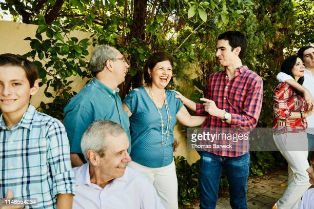 laughing aunt and uncle hanging out with nephew during backyard family party - zia e nipote foto e immagini stock